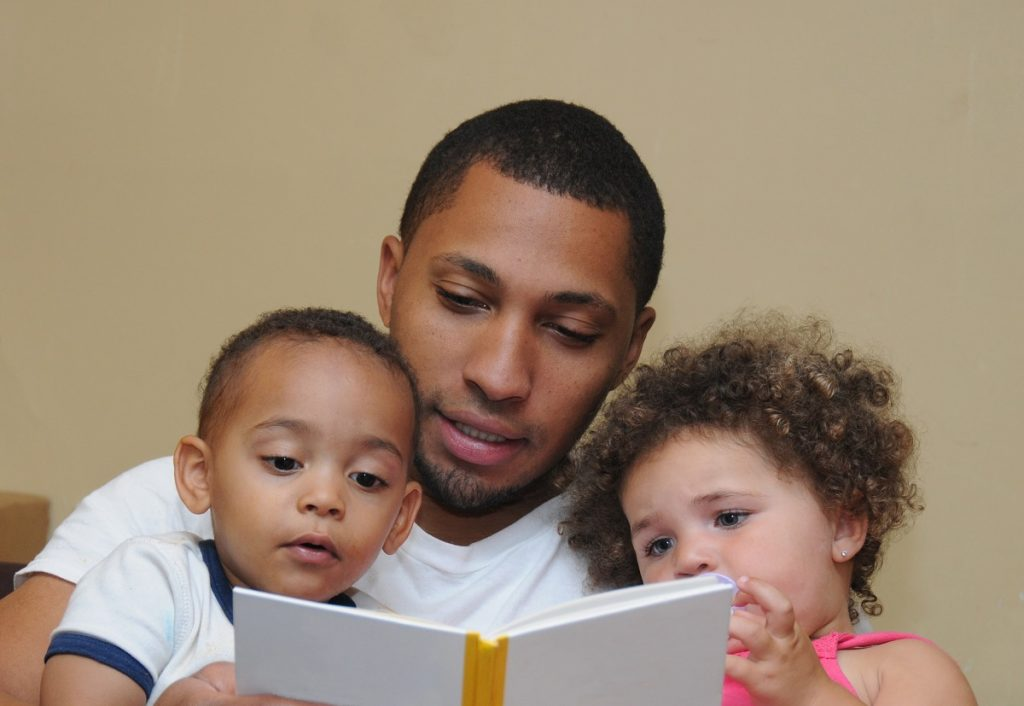 Father reading a storybook to his kids