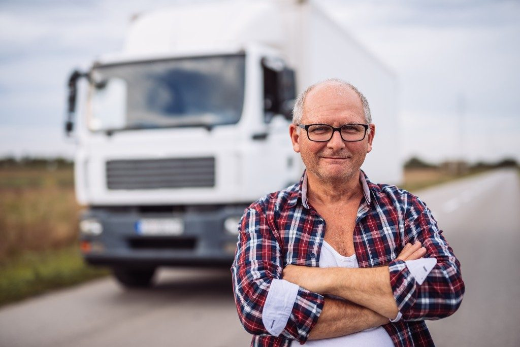 Middle aged driver posing with a truck on the background