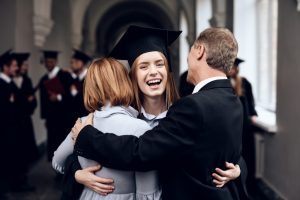 Student hugging her parents after graduating