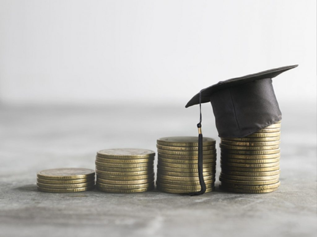 Stacked coins with graduation hat
