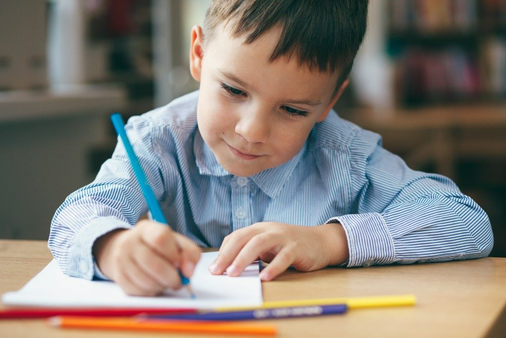a child writing on his desk