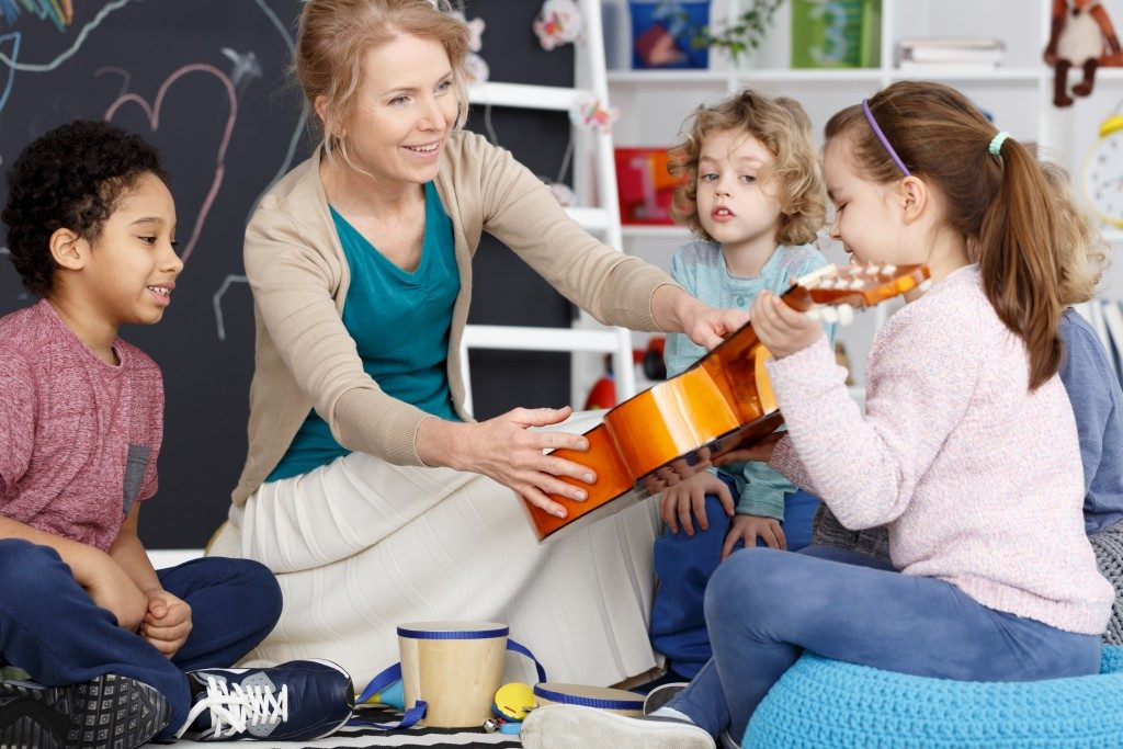 Instructor teaching students how to play the guitar