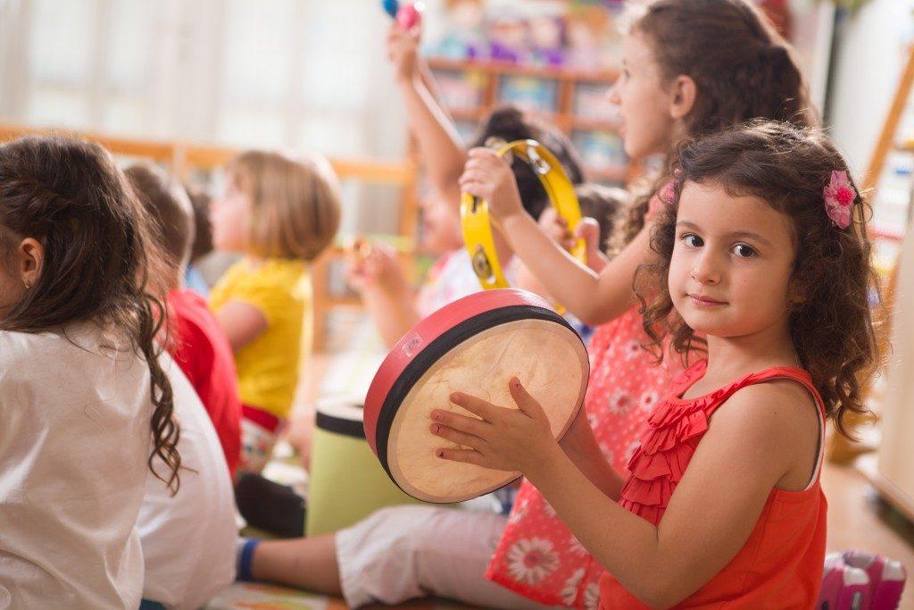 Little girl playing tambourine