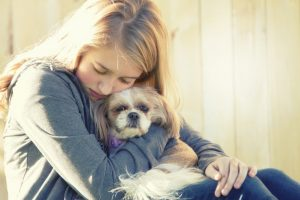 girl hugging her dog